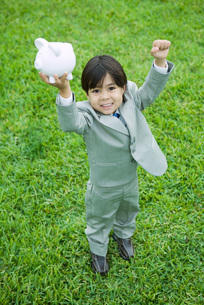 Boy holding up piggy bankの写真素材 [FYI04320817]