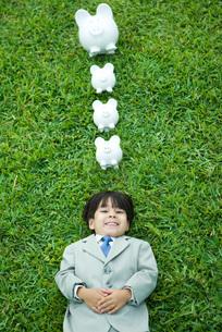 Boy in full suit lying on grassの写真素材 [FYI04320818]
