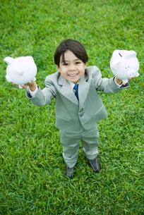 Boy holding up piggy banksの写真素材 [FYI04320820]