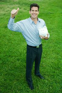 Man holding piggy bankの写真素材 [FYI04320821]
