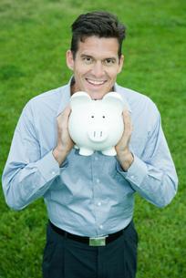 Man holding piggy bank under chinの写真素材 [FYI04320822]