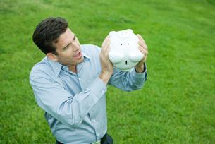 Man holding piggy bank upside downの写真素材 [FYI04320823]