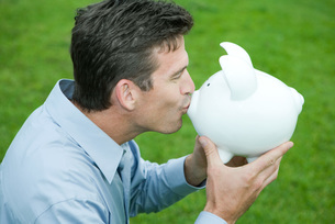 Man kissing piggy bankの写真素材 [FYI04320824]