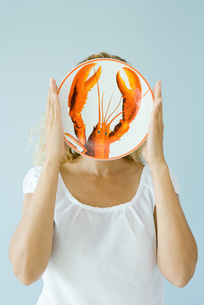 Woman holding up lobster plateの写真素材 [FYI04320827]