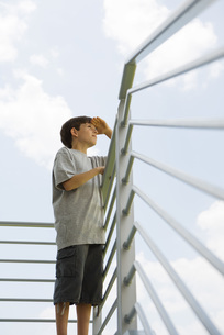 Boy standing on balcony, looking at viewの写真素材 [FYI04320836]