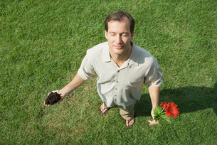 Man holding soil and flowerの写真素材 [FYI04320856]