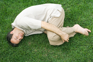 Man lying in fetal position on grass upの写真素材 [FYI04320868]