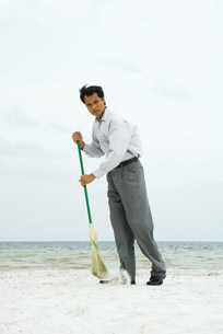 Man standing and sweeping with broomの写真素材 [FYI04320878]