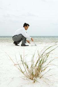 Man sweeping sand into dustpanの写真素材 [FYI04320879]