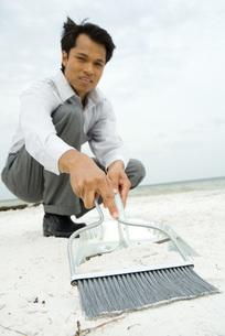 Man sweeping sand into dustpanの写真素材 [FYI04320880]