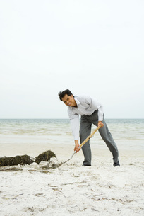 Man scooping sand with shovelの写真素材 [FYI04320881]