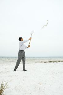 Man holding up shovel, throwing sandの写真素材 [FYI04320882]