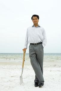 Man leaning against shovelの写真素材 [FYI04320884]