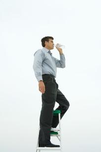 Man standing on top of ladderの写真素材 [FYI04320886]