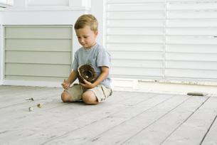 Boy spilling eggs out of bird's nestの写真素材 [FYI04320896]