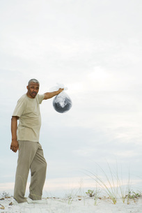 Man holding globe in plastic bagの写真素材 [FYI04320900]
