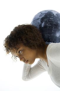 Woman carrying globe on shouldersの写真素材 [FYI04320920]