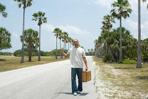 トランクを持って歩く男性の写真素材 [FYI04320931]
