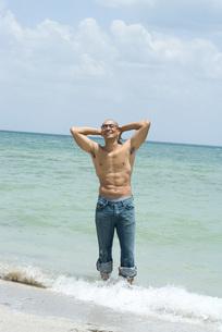 海で両手を頭の後ろに回す男性の写真素材 [FYI04320939]