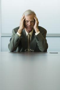 頭を抱えるビジネスマンの写真素材 [FYI04320951]