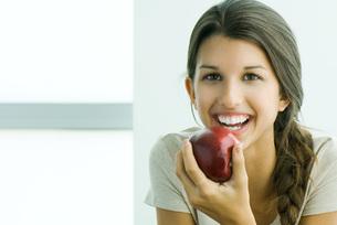 female holding apple at cameraの写真素材 [FYI04321020]