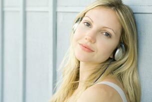 woman listening to headphones at cameraの写真素材 [FYI04321022]