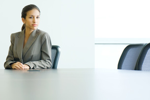 female in business suit sitting at tableの写真素材 [FYI04321026]