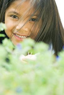 Girl smiling at camera, hair in faceの写真素材 [FYI04321038]