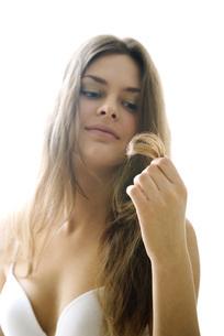 woman in bra looking at ends of hairの写真素材 [FYI04321072]