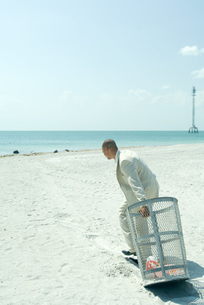 Man in suit pulling garbage canの写真素材 [FYI04321088]