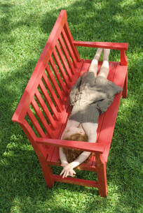 girl lying on red bench in shadeの写真素材 [FYI04321091]