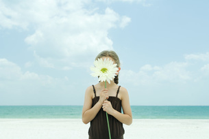 Girl holding up flower in front of faceの写真素材 [FYI04321093]