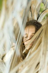 Woman closing eyes, hair blowing in windの写真素材 [FYI04321105]