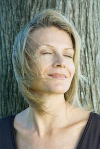 Woman smiling, hair blowing in windの写真素材 [FYI04321112]