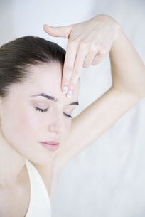 woman touching foreheadの写真素材 [FYI04321116]