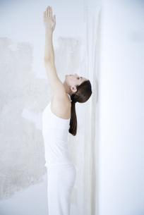 Woman standing, stretching, arms raisedの写真素材 [FYI04321123]