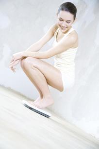 woman crouching on bathroom scaleの写真素材 [FYI04321128]