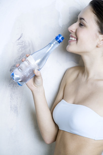 woman holding up water bottleの写真素材 [FYI04321143]