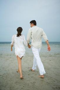 Couple walking hand in hand on beachの写真素材 [FYI04321179]