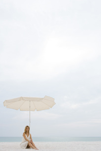 Woman sitting under parasol on beachの写真素材 [FYI04321249]