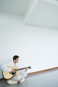 man sitting on floor, playing guitarの写真素材 [FYI04321254]