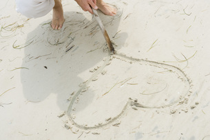 Man tracing heart in sand with stickの写真素材 [FYI04321266]