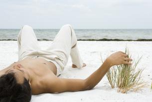 man lying and touching dune grassの写真素材 [FYI04321271]