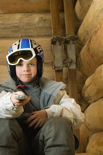 Boy in ski gear pointing remote controlの写真素材 [FYI04321279]