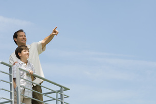 Man standing on balcony with sonの写真素材 [FYI04321316]