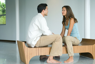 couple sitting face to face on benchの写真素材 [FYI04321320]