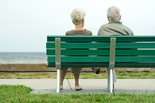 Couple sitting on bench looking at oceanの写真素材 [FYI04321321]