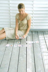 Woman sitting on deck playing cardsの写真素材 [FYI04321356]