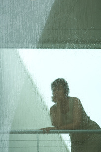 Woman looking through window in rainの写真素材 [FYI04321357]