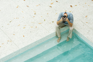 Man sitting with feet in poolの写真素材 [FYI04321358]